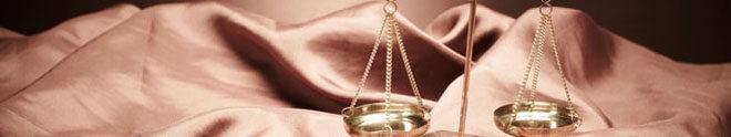 gold scales of justice on light brown gathered material used as header to practice areas